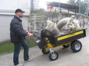 Brouette électrique avec plateau transportant des sacs dans une pente
